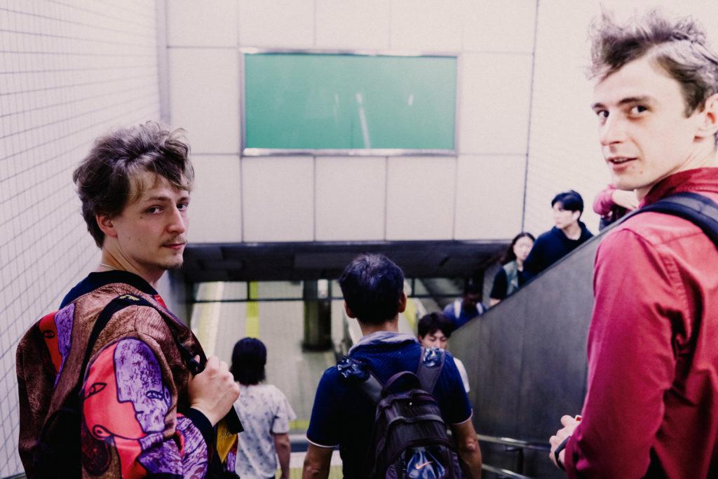 Daniel, der Autor des Arikels, befindet sich auf einer Treppe, die Hinunter in eine U-Bahn führt, japanische Zeichen lassen darauf schließen, dass das Foto in Japan aufgenommen wurde. Er wird begleitet von einem jungen Franzosen, der ebenfalls in die Kamera schaut. Daniel trägt eine bunte Jacke, einen Bart und seine Haare sind von Wind verwuschelt.